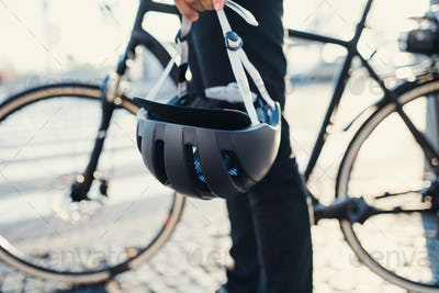 Midsection of commuter with electric bicycle and helmet traveling in city.