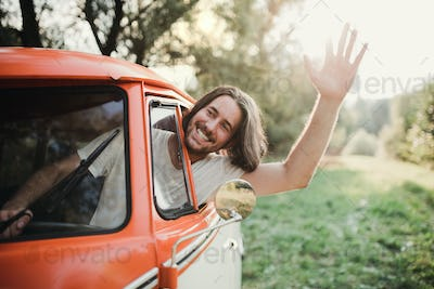 A young man driver in a car on a roadtrip through countryside, waving.