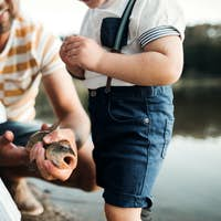 A midsection of father with small toddler children fishing by a lake, holding a fish.
