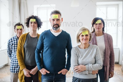 Young and old people standing with negative emotions adhesive notes during group therapy.