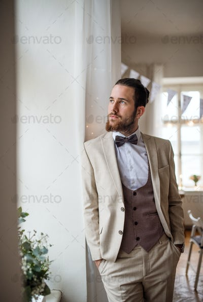 A handsome hipster young man with formal suit standing by window on an indoor party.