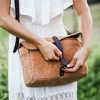 A midsection of woman standing in nature with a brown leather bag.