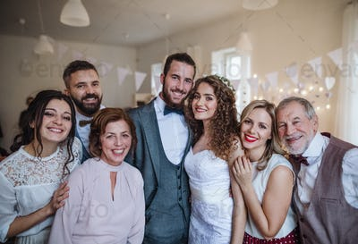 A young bride, groom and guests posing for a photograph on a wedding reception.