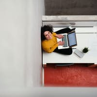 A top view of young businesswoman sitting on desk in an office, using laptop.