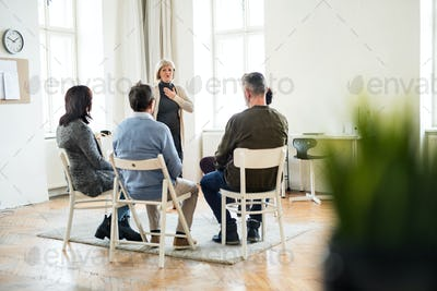 A woman talking to other people during group therapy.