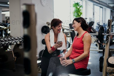 Two senior women in gym resting after doing exercise, holding smartphone.