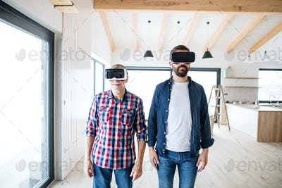 A man with VR goggles and his senior father furnishing new house, a new home concept.