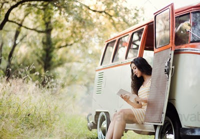 A young girl with a book by a car on a roadtrip through countryside, reading.