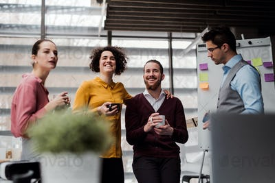 A group of young businesspeople with cup of coffee standing in office, talking.