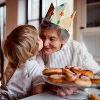 Senior grandmother with small toddler boy making cakes at home, kissing.