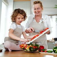 A portrait of small girl with grandmother at home, preparing vegetable salad.