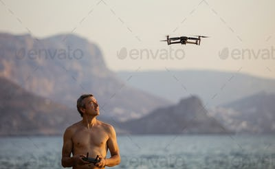 Caucasian man operating drone by remote control at sea shore