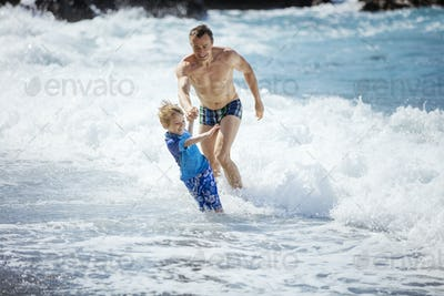 Father and son playing on the beach in rough water