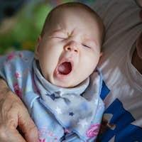 Baby girl yawning. Grandfather rocking baby to sleep.