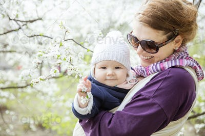 Young woman carrying her baby daughter in woven wrap outdoors