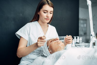 Beautician makes face mask to young woman