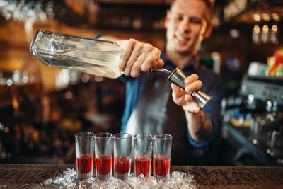 Male barman in apron prepares alcoholic coctail