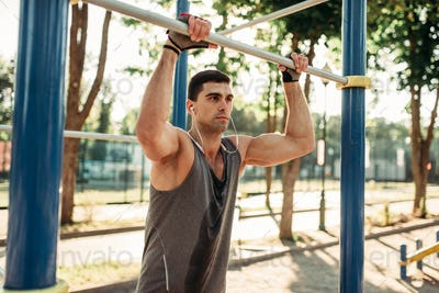 Male athlete poses on horizontal bar outdoor