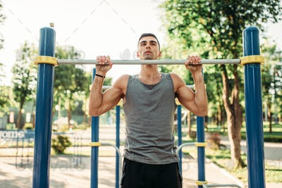 Athlete doing exercise on horizontal bar outdoor