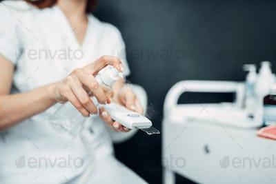 Female beautician hands prepares equipment