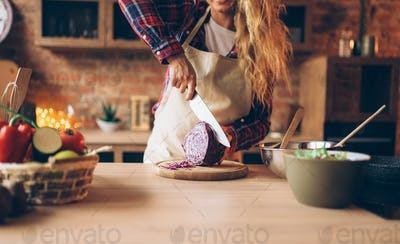 Female cook in apron cutting fresh vegetables