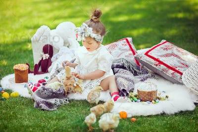 Child Sits on a Meadow Around Easter Decoration