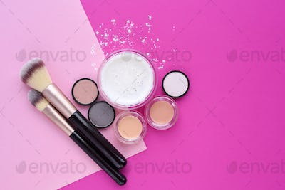 Mineral powder foundation and make-up brushes on bright pink bac