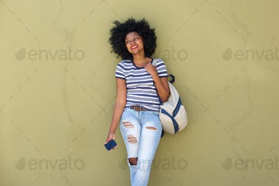 happy woman with mobile phone smiling with bag