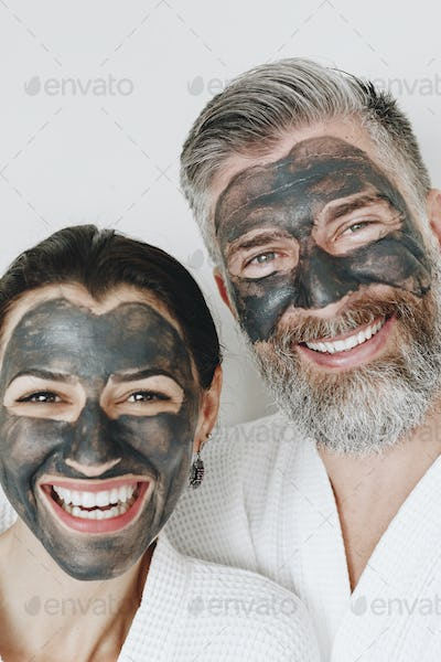 Happy couple wearing a charcoal mask
