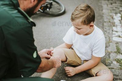 Injured boy getting help from paramedics