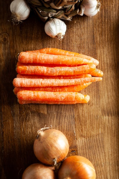 Top view of fresh carrots next to white onion and garlic on rustic wooden table
