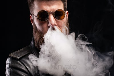 Attractive bearded man exhaling cigarette smoke on his nose over black background