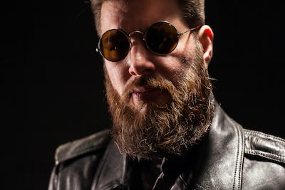 Close up portrait of serious handsome bearded man over black background