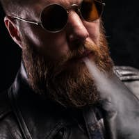 Low key portrait of attractive bearded man over black background