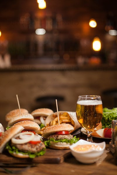 Tasty different burgers and a glass of cold beer on wooden table