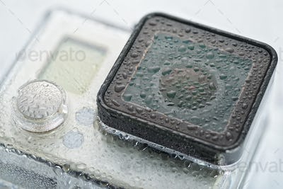 Action camera lens with water drops