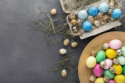 Colored Easter and quail eggs set on black table