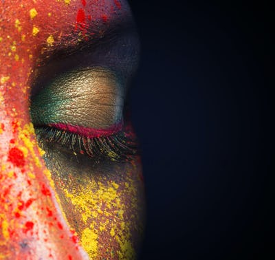 Closed female eye with colorful makeup on black