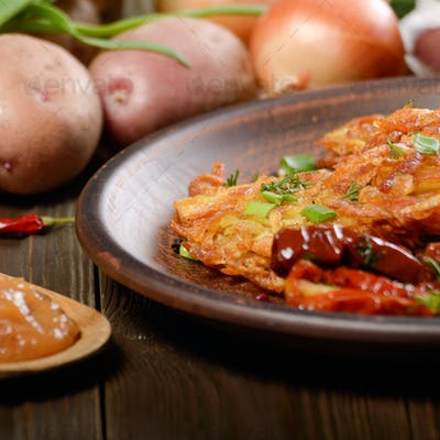 Homemade tasty potato pancakes in clay dish with applesauce