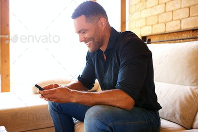 Portrait of young man sitting on sofa and using mobile phone at home