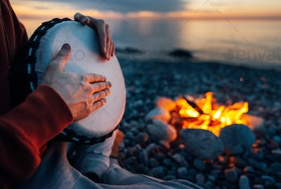 percussionist plays djembe on the seashore near fire, hands clos