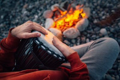 percussionist playing djembe sitting by fire, close-up