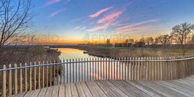 Wooden deck balustrade sunset over swamp