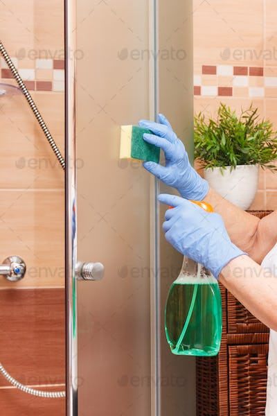 Hand of senior woman with sponge and detergent cleaning glass shower door, household duties concept
