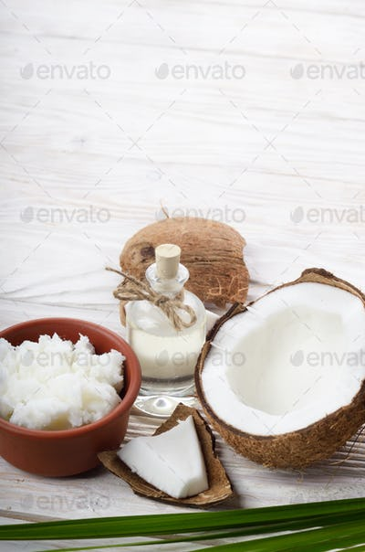 Background of coconut, coconut shell, oil in clay bowl and glass