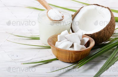 Coconut shell hard oil in glass jar and coconut meat pieces in b