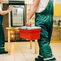Male workers in uniform repair refrigerator