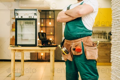 Worker in uniform against refrigerator on table