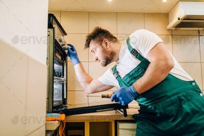 Repairman in uniform checks the oven, technician