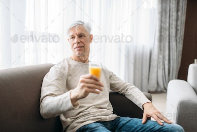Cheerful adult man drinks fresh juice